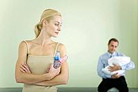 Woman holding baby bottles, looking over shoulder at husband holding baby in background