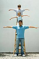 Boy and girl standing on ladder with arms in the air, father standing on the ground, all smiling at camera