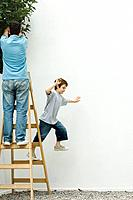 Father and son standing on ladder, boy leaping off