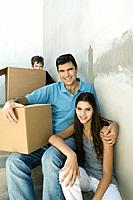 Father and teen daughter on stairwell with cardboard boxes, boy hiding in background (thumbnail)