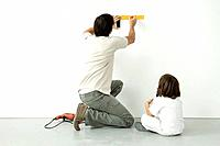 Man measuring wall with a ruler while his son watches, drill on the floor nearby (thumbnail)