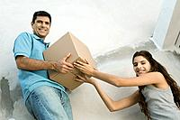 Father and daughter moving cardboard box together, low angle view