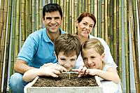 Family together, parents smiling at camera, children touching potted seedling