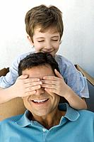 Boy with hands over his father's eyes, both smiling, boy's eyes closed