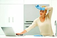 Woman standing at kitchen sink, reaching for laptop computer, wearing rubber gloves