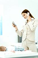 Professional woman talking on phone, looking at self in mirror compact, baby lying on desk nearby