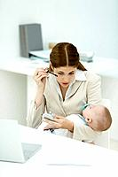 Professional woman in office, applying mascara, holding sleeping baby