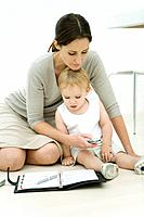 Professional woman sitting on the ground with toddler and agenda, dialing cell phone