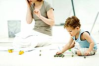 Little boy sitting on the ground, playing marbles, mother surrounded by paperwork in background