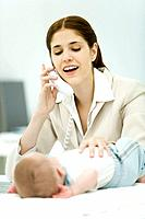 Professional woman touching infant lying on desk, making phone call, smiling