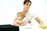 Professional woman sitting at breakfast table, holding toddler and keys
