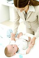Young professional mother changing infant's diaper