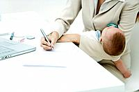 Professional woman signing document at desk, holding sleeping infant, cropped view