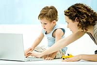 Mother and young son using laptop computer together