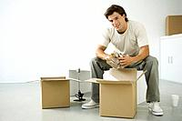 Man unpacking boxes, sitting on bench, smiling at camera
