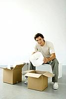 Man unpacking boxes, holding lampshade, smiling at camera