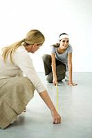 Mother and daughter using measuring tape on the floor