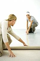 Mother and daughter installing carpet together