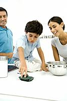 Boy playing with toy tank on kitchen counter, parents looking on and smiling