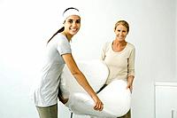 Mother and daughter carrying chair covered in bubble wrap, smiling at camera