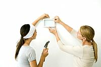 Mother and daughter attaching picture frame to wall