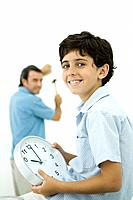 Boy holding clock and smiling at camera, father holding hammer in background