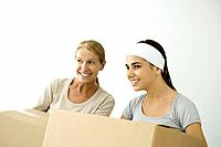 Mother and daughter holding cardboard boxes, both smiling and looking away