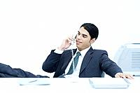 Young businessman sitting with feet up at desk, talking on landline phone