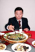 Businessman eating chinese cuisine