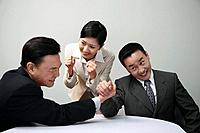 Businessmen arm wrestling with businesswoman cheering