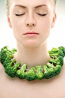Woman with a string of broccoli around her neck