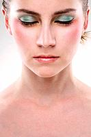Woman with sparkling eyeshadow closing her eyes