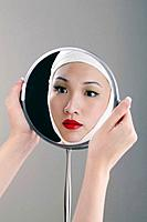 Woman with bandaged face looking into a mirror