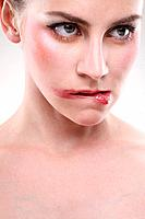 Woman with smudged lipstick biting her lower lip