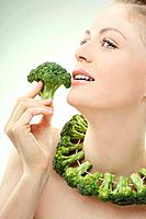 Woman with a string of broccoli around her neck, holding a broccoli