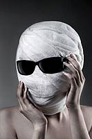 Woman with bandaged face wearing sunglasses