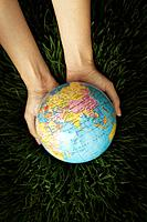 Human hand holding globe on grass