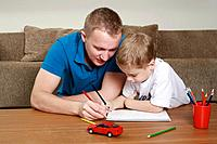 Man and boy drawing on notebook