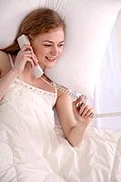 Woman talking on the phone while lying on the bed