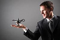 Businessman holding magic lamp