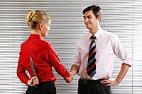 Businessman and businesswoman shaking hands, businesswoman hiding knife behind her back