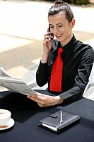 Businesswoman talking on the mobile phone while reading newspaper (thumbnail)