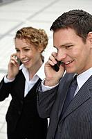 Businessman and businesswoman talking on the phone (thumbnail)
