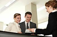 Receptionist passing a letter to businessman and businesswoman