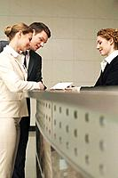 Receptionist showing letter to businessman and businesswoman