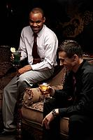 Businessmen sitting on antique sofa talking while having cocktails