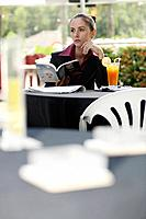 Businesswoman holding a book while in deep thought, looking away