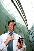 Businessman smiling while text messaging on the phone (thumbnail)