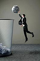 Businessman dunking a giant sized crumpled paper into a big dustbin