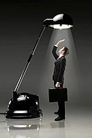 Businessman standing under an illuminating table lamp